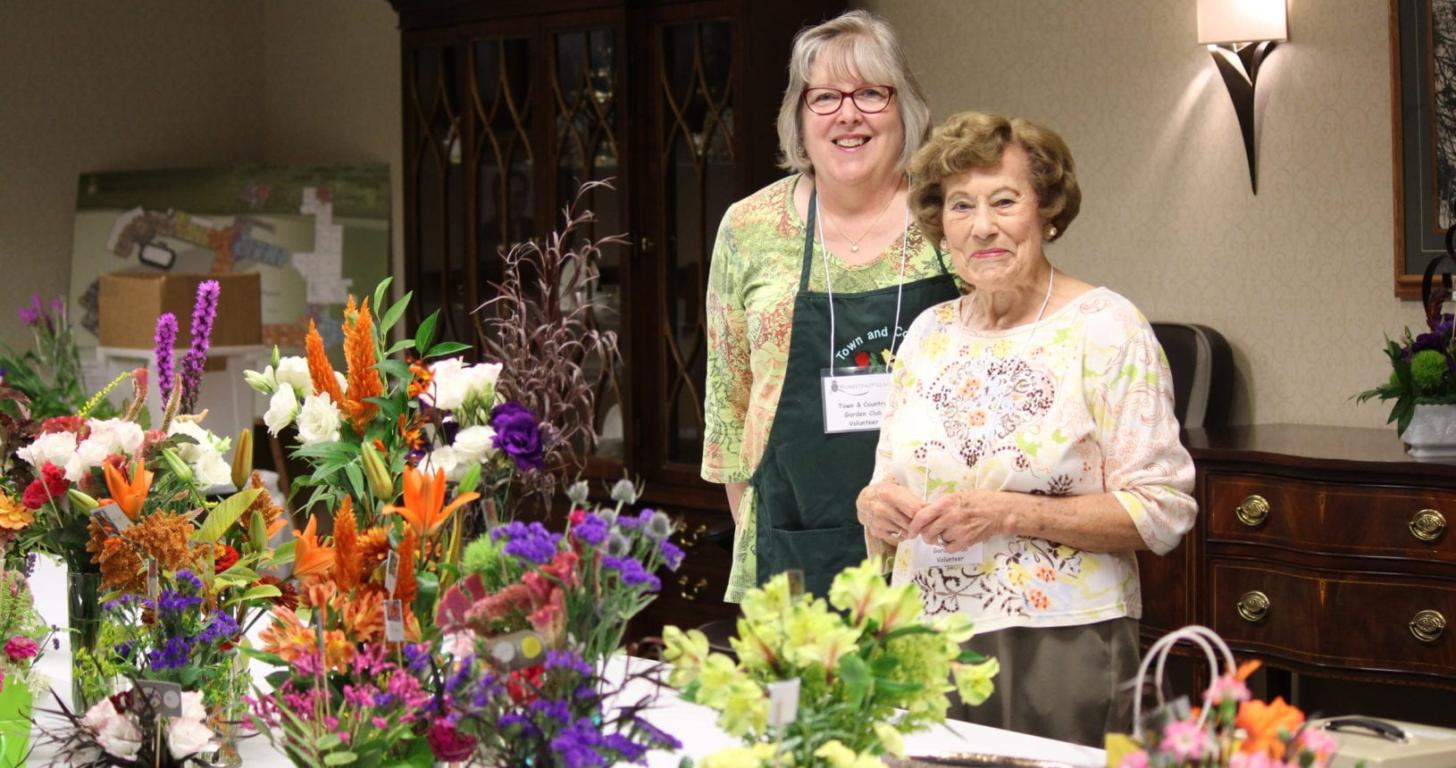 Ladies showing flower arrangements at the Homestead Day Plant Sale