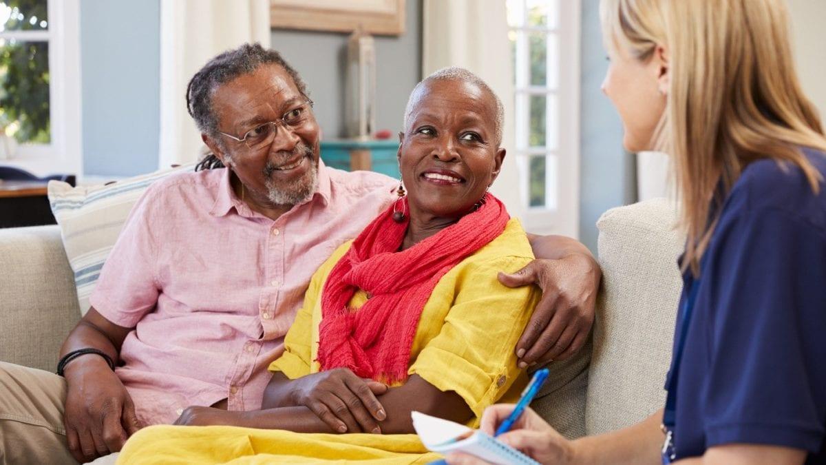 senior couple talking to a nurse