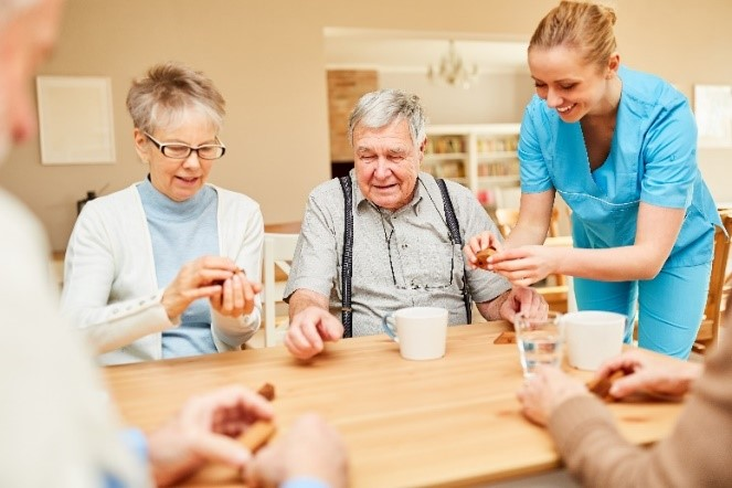 Personal care residents sitting around a table in a common area