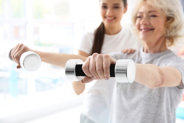 woman working with weights in a physical therapy session at a CCRC