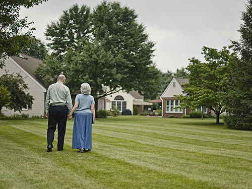 A retired couple walks hand in hand on green grass surrounded by trees and homes