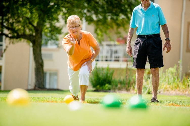 A woman throws a Bocce ball while her male partner watches