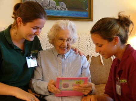 A woman shows two staff members at Homestead Village her photo album