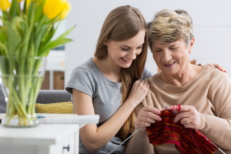 An older woman knitting while a caregiver holds her shoulders.