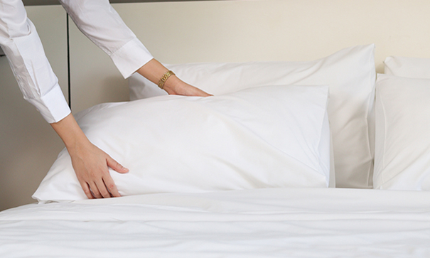 A senior care provider makes the bed for her clients.